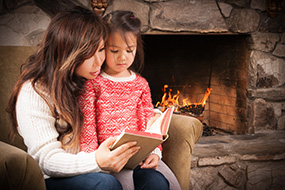 mother reading to child next to fireplace